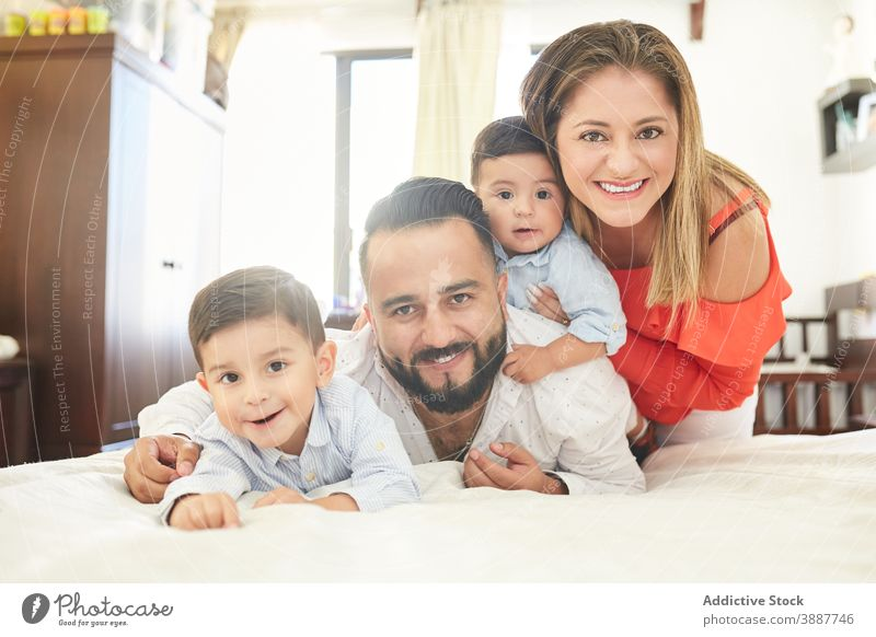 Cheerful ethnic family on bed at home gather having fun pastime together couple son sibling hispanic relationship love fondness kid child cuddle affection enjoy
