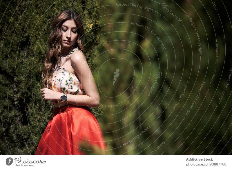 Elegant woman in dress walking along path in park grace garden elegant charming appearance style outfit wavy hair long hair model trendy idyllic tranquil