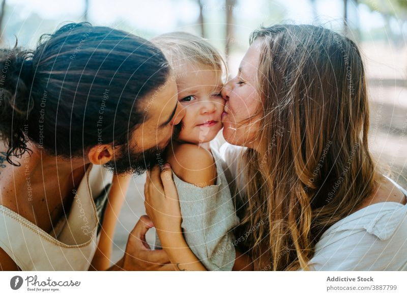 Mother and father kissing kid together family cheek child love mother cuddle unity multiethnic multiracial diverse forest hug tender daughter parent happy