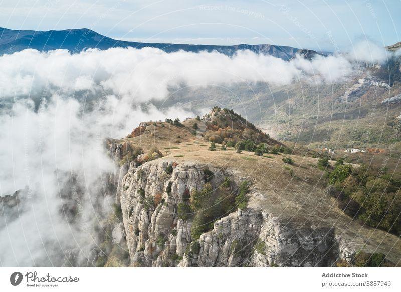 Mountain ridge with dense white clouds mountain rock range landscape nature hill picturesque autumn rocky highland environment travel tourism terrain steep