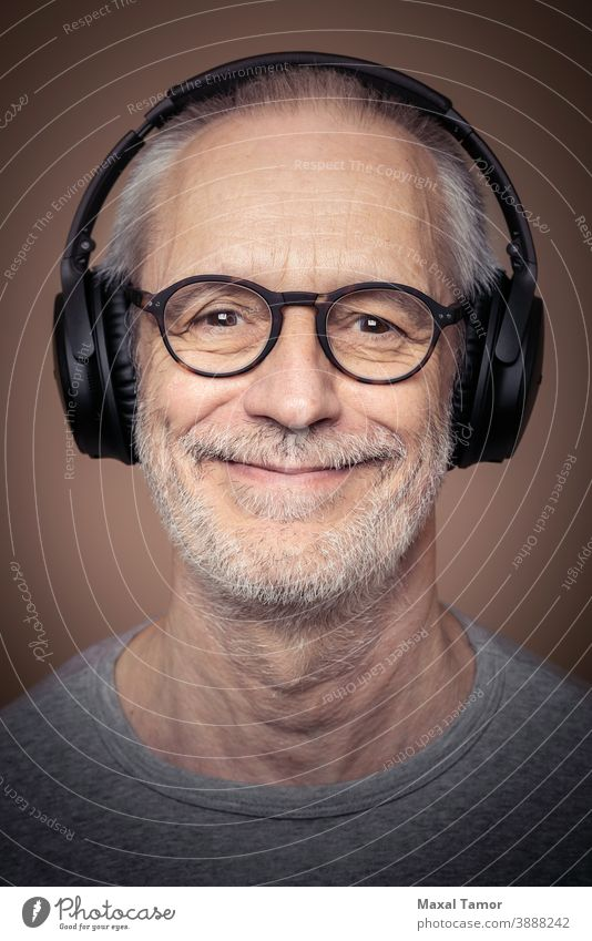 Portrait of adult man with beard wearing stereo headset and glasses. attractive audio boy casual caucasian cheerful concept cool device digital earphones