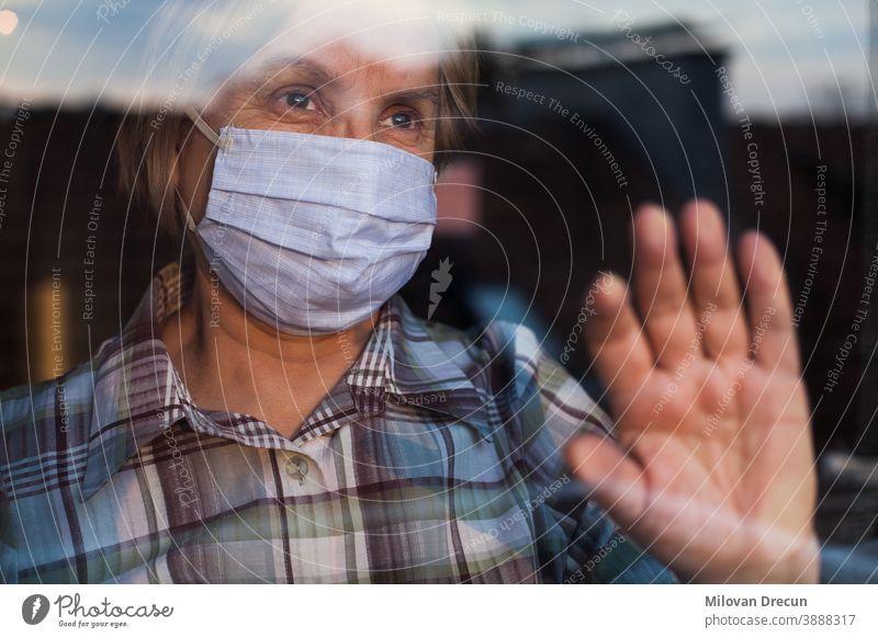 Elderly caucasian woman wearing hand made protective face mask anxious care contagious corona coronavirus covid-19 crisis depressed depression disease epidemic