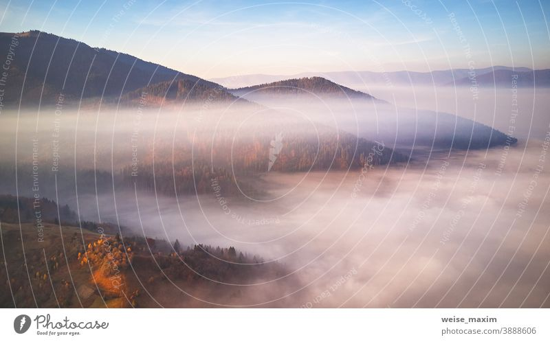Beautiful Autumn mountain panorama. Morning thick fog cover valley aerial view. Fantastic fall sunrise autumn landscape forest travel mist morning season nature