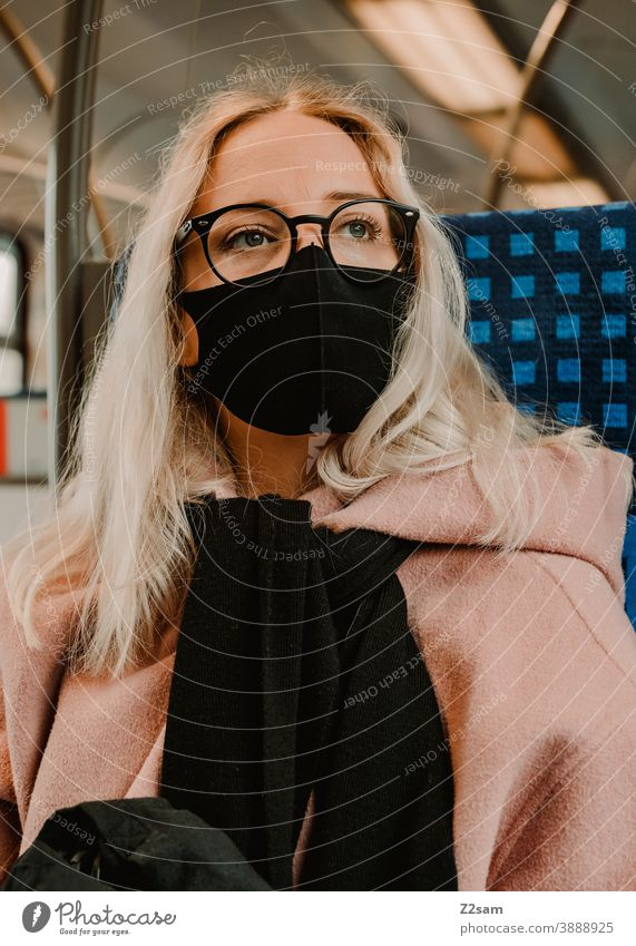 Young woman sitting in the train with a corona mask coronavirus Blonde long hairs Track voyage Company Winter Coat Eyeglasses Fashion style Looking pretty