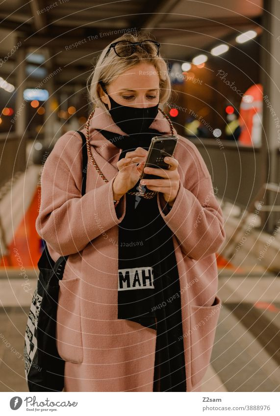 Young woman standing at the station with a corona mask coronavirus Blonde long hairs Track voyage Company Winter Coat Eyeglasses Fashion style Looking pretty