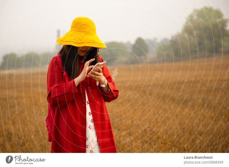Girl with red trench and yellow hat using mobile phone in a cropped field woman nature autumn outdoors people beauty beautiful portrait summer person happy