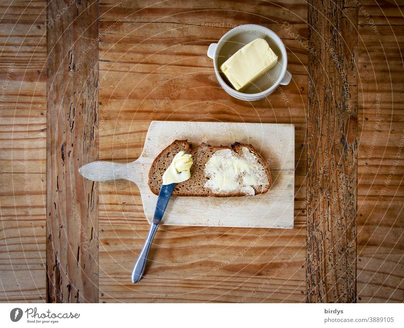 Bread and butter on vesper board on wooden table. Bird's eye view Butter snack Wooden table Knives Butter bowl Delicious Mixed-grain bread Authentic Brunch