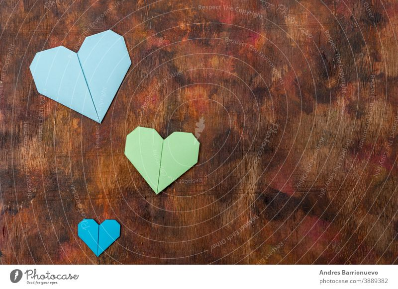 Origami hearts made with colored paper for congratulations on Valentine's Day for couples in love, on an old wooden background in brown tones board green