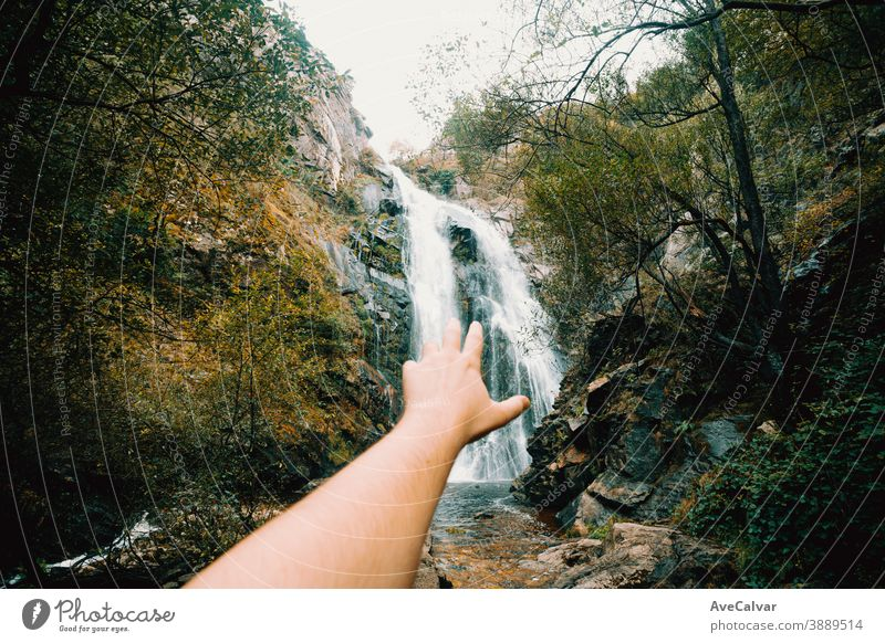 Horizontal shot of an out of focus hand reaching a massive waterfall nature tree western serene scenery natural peaceful foliage landscape cascade forest