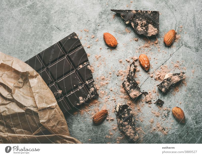 Dark chocolate bar and Broken chocolate pieces and almonds yummy confectionery envelope dark chocolate broken antioxidant cacao powder candy calorie eating