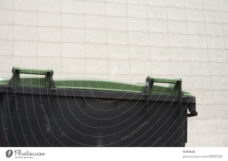 Detail of waste container with green plastic lid in front of a light-coloured facade with rectangular panels Trash container Large detail Plastic Facade