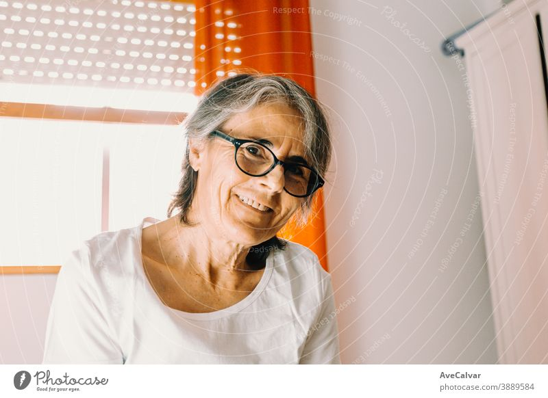 Close up of a old woman with glasses smiling to camera in a bright bedroom person grandmother lady mature pensioner senior smile looking portrait 50s clinic