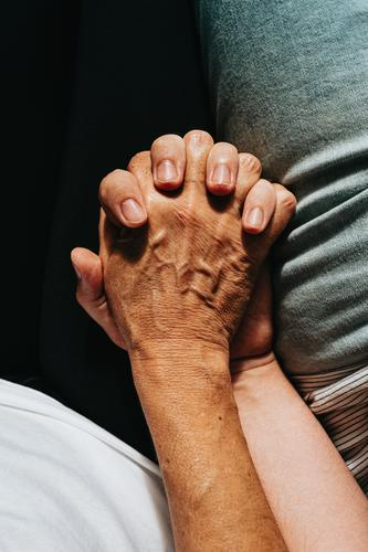 Close up of an old hand grabbing a young hand on cinematic tones assistance community females friendship grandparent holding hands horizontal reaching touching
