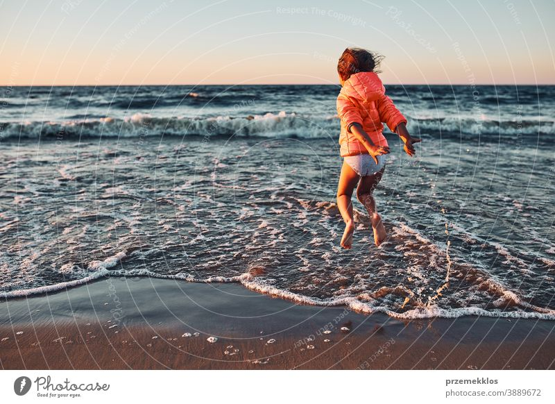 Playful little girl jumping over sea waves on a sand beach at sunset excited free enjoy positive emotion carefree nature outdoors travel happiness happy summer