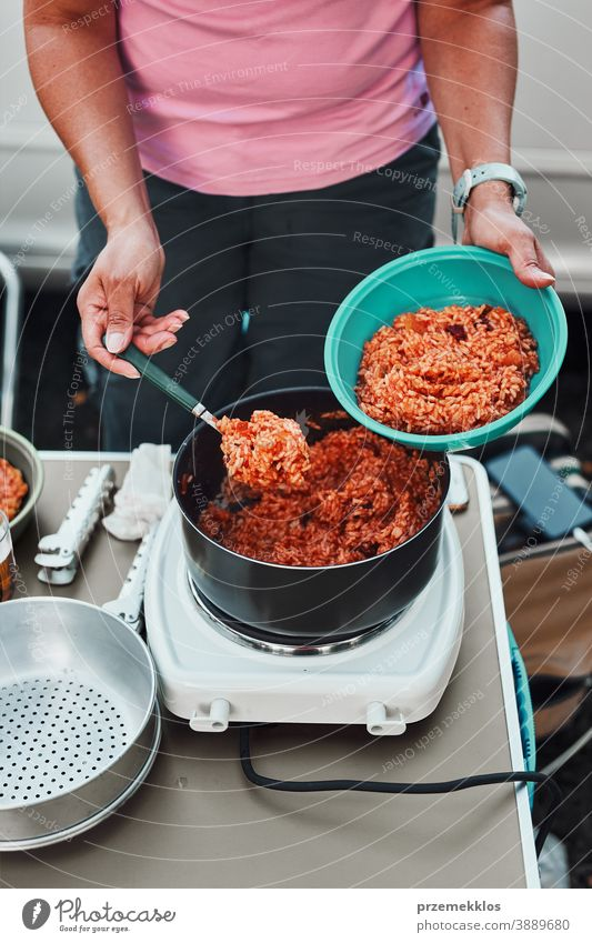 Woman putting rice dish with tomato sauce to a bowl on summer vacations on camping lunch outdoor cooking cuisine hot pot meal female dinner eating recreation