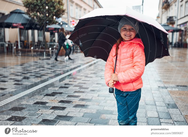 Little girl holding big umbrella walking in a downtown on rainy gloomy autumn day raining outdoors little seasonal fall childhood beautiful weather outside kid