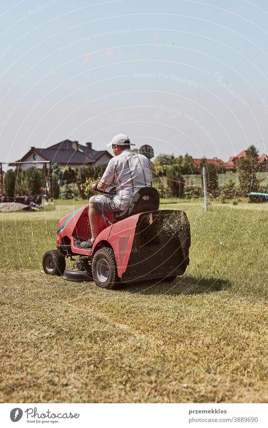 Man mowing his lawn using riding lawnmower occupation seasonal cut trimming man job person field professional ride gardener drive equipment worker male