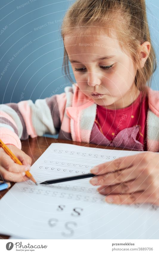 Little girl preschooler learning to write letters with help of her mother attention caucasian child childhood cute education educational fun home kid little