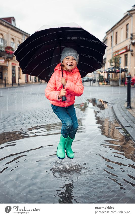 Little girl holding big umbrella jumping in the puddle on rainy gloomy autumn day raining outdoors little seasonal fall childhood beautiful weather outside kid