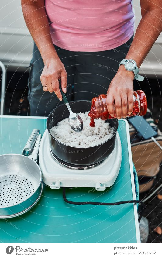 Woman cooking meal on electric stove on camping during summer vacations rice dish lunch outdoor cooking cuisine hot pot female dinner eating recreation trip