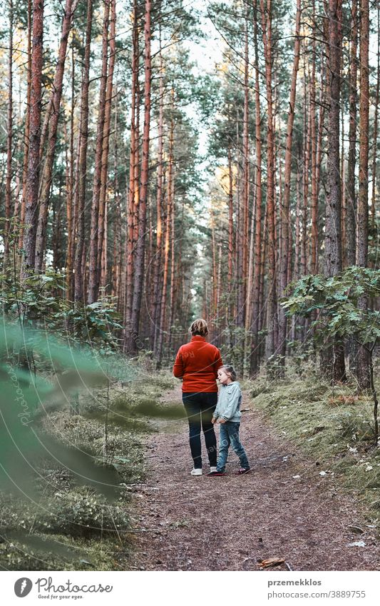 Mother and her little daughter walking in a forest during summer vacation trip active activity destination enjoy exploration female green hike lifestyle nature