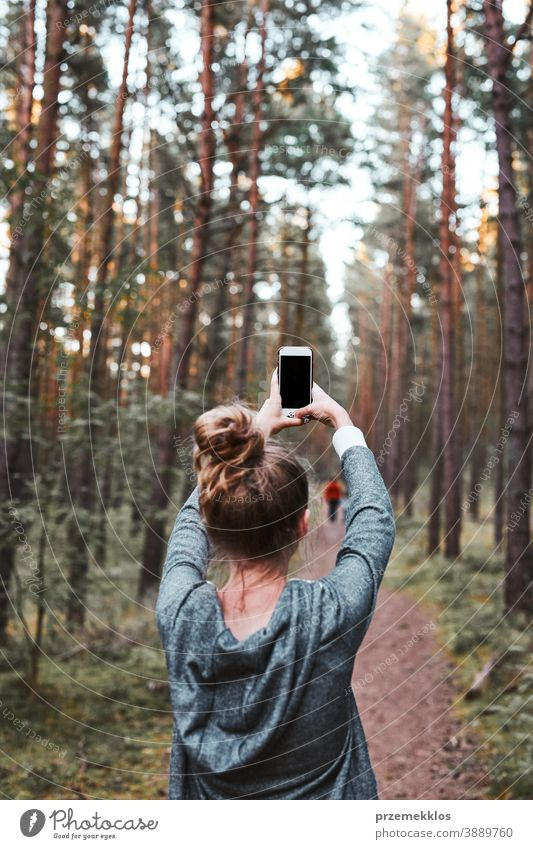 Young woman taking photos using smartphone during walk in a forest on summer vacation trip active activity destination enjoy exploration female hike lifestyle