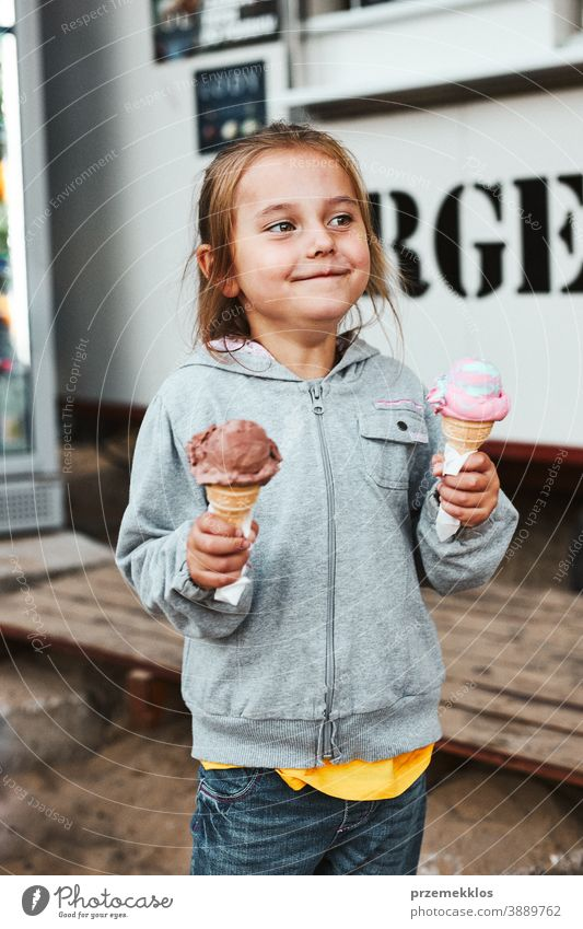 Happy smiling little girl holding two ice cream standing in front of food truck vacation family time family vacation spending time buying shop cafe lifestyle