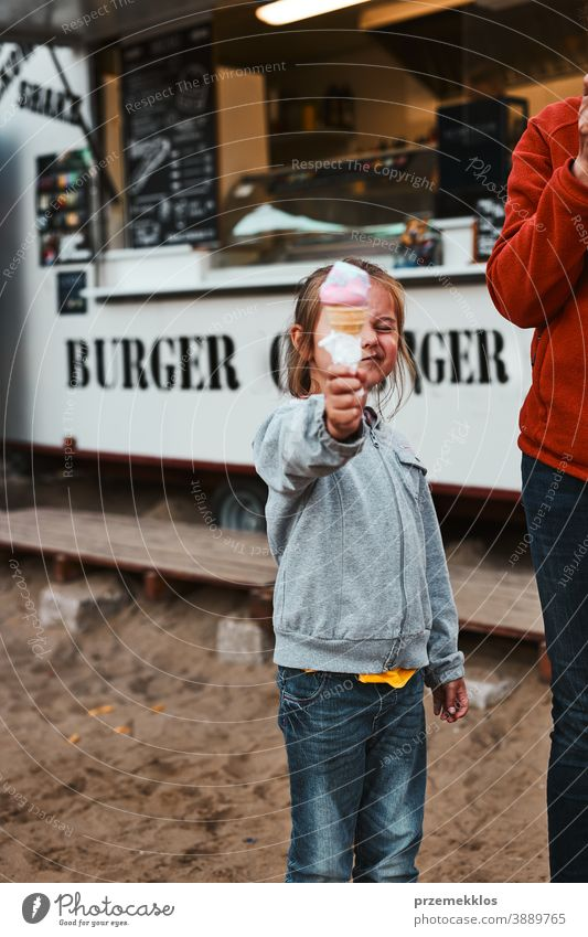 Little girl holding her ice cream in front of her face standing in front of food truck people vacation family time family vacation spending time buying shop