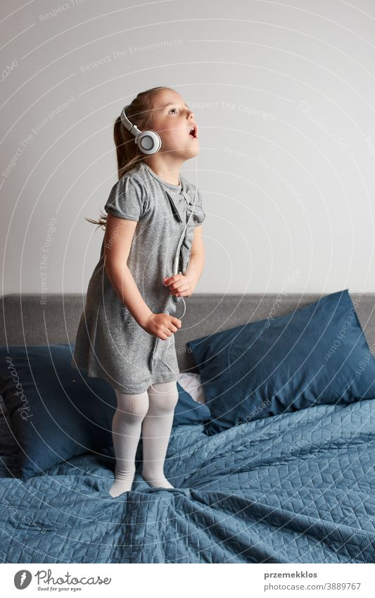 Little girl singing dancing imitating herself a real singer child jumping playing listening fun happy home bed childhood portrait natural dance pretend