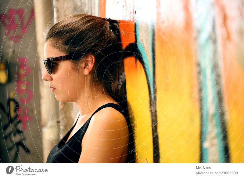 Teen leans relaxed against a graffiti wall Graffiti Wall (building) Wall (barrier) Girl Sunglasses portrait Hair and hairstyles Looking Authentic Orange