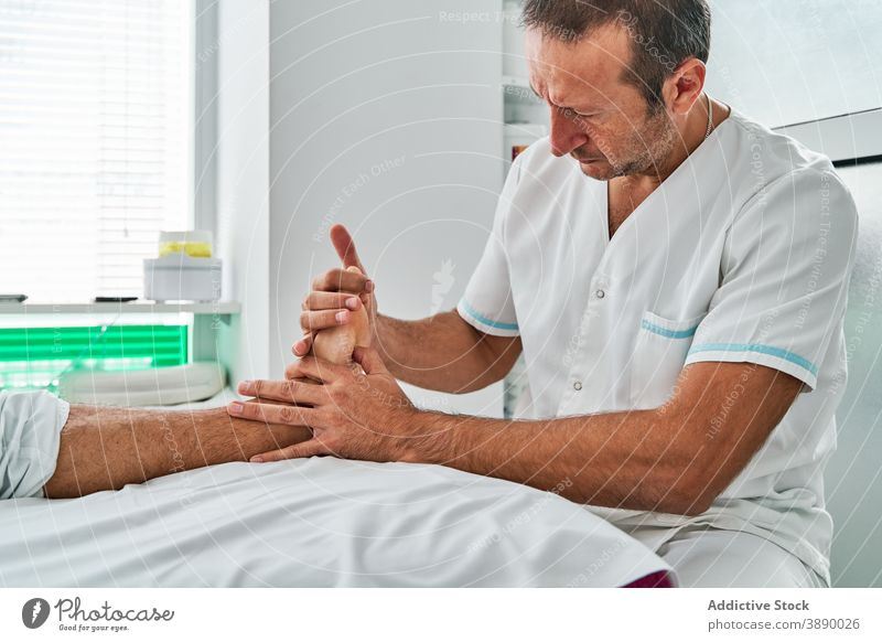 Male osteopath massaging feet of patient in hospital massage osteopathy physiotherapy therapist masseur medical session clinic table lying rehabilitation treat