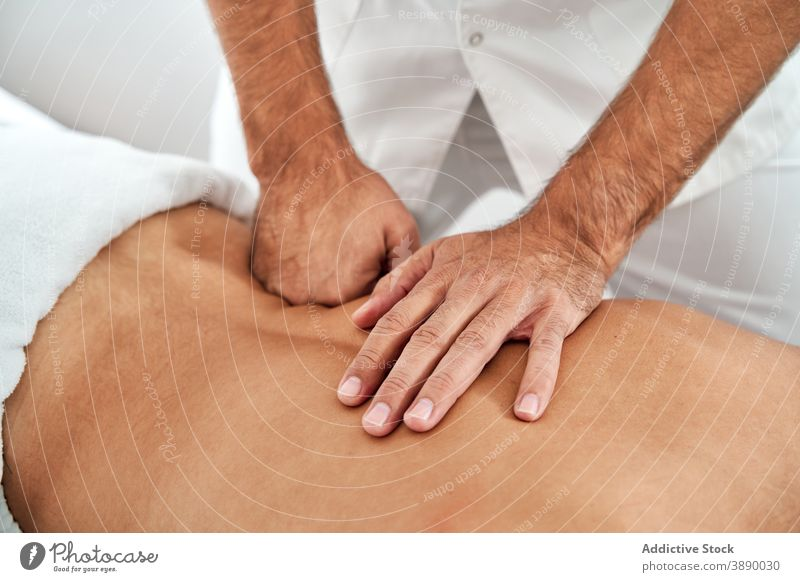 Crop male osteopath doing massage for patient in hospital physiotherapy therapist masseur rehabilitation session health care lying medical table back doctor