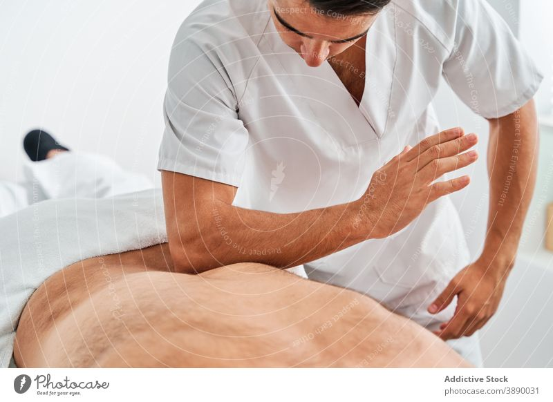 Male massage therapist treating client in hospital osteopath back physiotherapy masseur clinic patient bright medical rehabilitation procedure room help visit