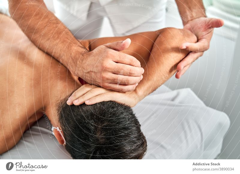 Crop massage therapist massaging arms of client osteopath treat physiotherapy masseur patient clinic doctor modern table lying health care work job procedure