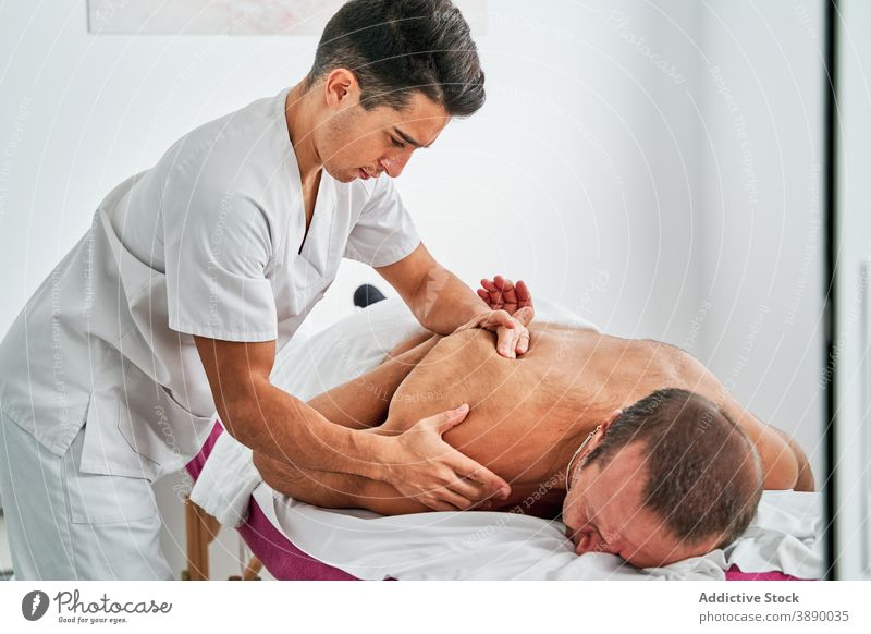 Osteopath doing massage for patient in hospital osteopath physiotherapy therapist masseur rehabilitation session health care lying medical table back doctor
