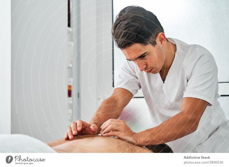 Physiotherapist doing massage for patient in clinic osteopath physiotherapy neck doctor back masseur medical mask lying table coronavirus covid 19 care pandemic