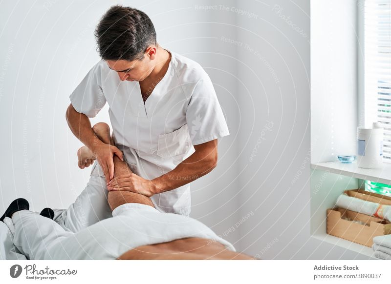 Therapist treating patient with massage in hospital therapy osteopath rehabilitation feet masseur therapist session medical bright room clinic osteopathy client