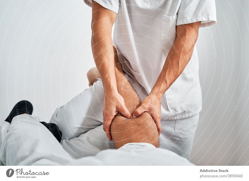 Therapist treating patient with massage in hospital therapy osteopath rehabilitation calf feet masseur therapist session medical bright room clinic osteopathy