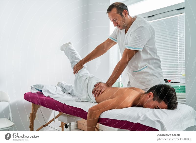 Male osteopath treating patient in modern clinic massage leg doctor rehabilitation contemporary procedure hospital practitioner aid medical help medicine