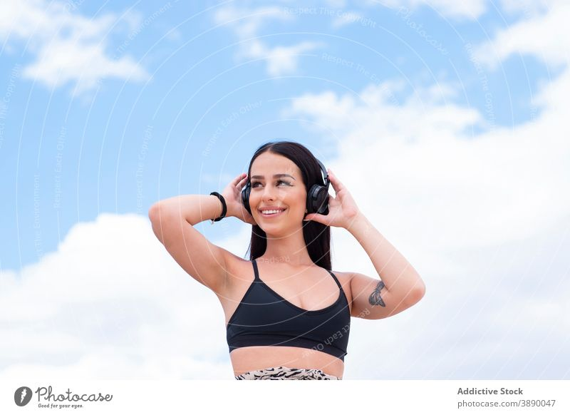 Happy woman with headphones on street fit using happy cheerful listen active positive young music wireless mobile workout gadget device lifestyle sportswoman
