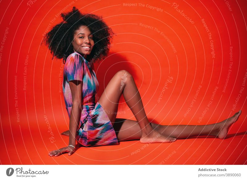 Charming black woman in vivid dress in studio cheerful bright laugh colorful trendy fun fashion toothy smile millennial ethnic afro african american cuban