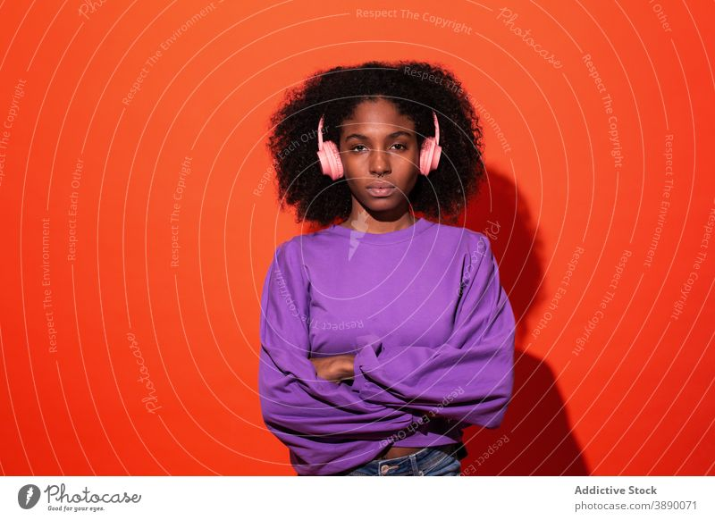 Emotionless African American woman in headphones music vivid listen style emotionless unemotional cool model millennial sound trendy female afro ethnic