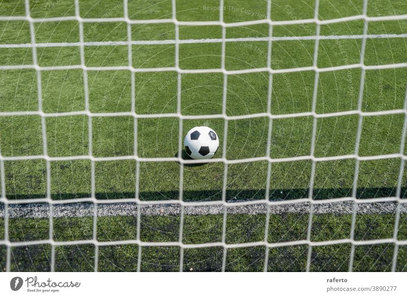 Vintage Soccer ball on green football field grass against net soccer goal no people background outdoor play pitch nobody game sport soccer field retro line