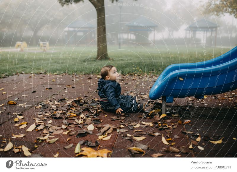 Toddler playing at playground Autumn Authentic Winter fall Playing Playground Slide Park Kindergarten Exterior shot Joy Colour photo Day Infancy