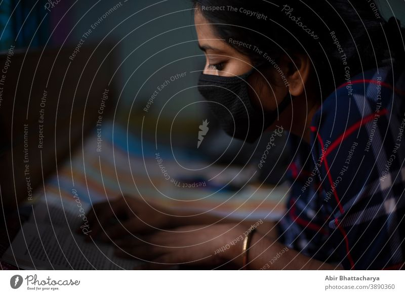 An Indian young woman with Corona preventive mask lying on bed at home with a laptop home isolation due to covid - 19. Indian lifestyle and disease. adult aged