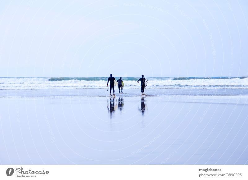 Surfers, carrying surfboards, walking into the water in Cornwall, UK surfers beach reflection cornwall wet sand active uk lifestyle adventure atlantic activity