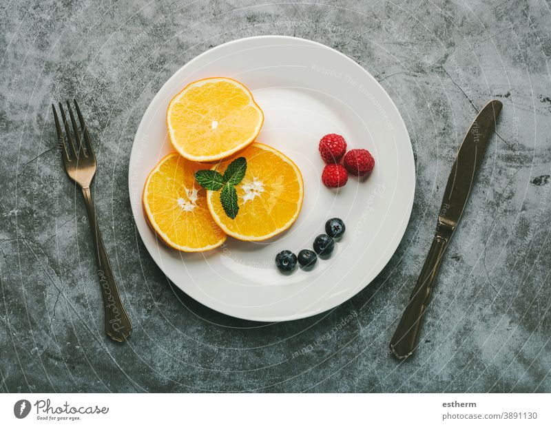 Healthy dessert.White plate with orange slices,raspberries,blueberries and vintage old cutlery healthy breakfast healthy dessert raspberry fitness fruit nature