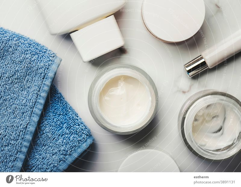 Skincare products.Cream jars,lotion, exfoliating cream and a blue towel dermatology hygiene brush cosmetic product health packaging container body tube