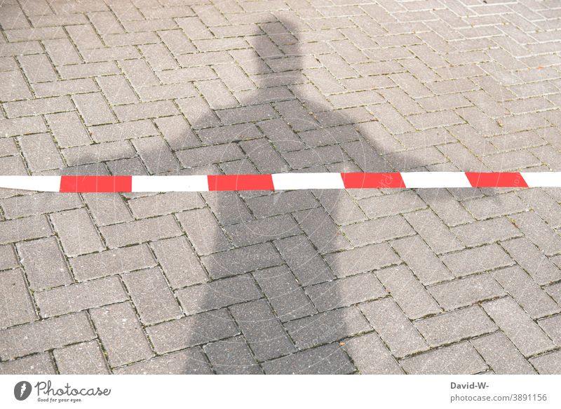 locked - shadow of a man behind the barrier tape cordoned off Man silouette interdiction Barred Shadow person flutterband insulation