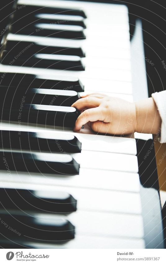 the hand of a child on the piano Piano Child Toddler Music Musical instrument Parenting Play piano Curiosity Hand Make music Cute